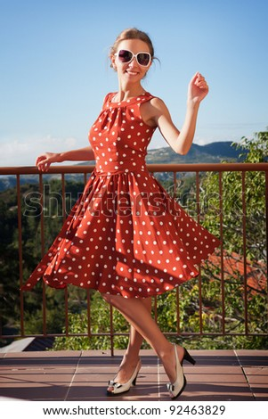 A beautiful girl in stylish dress having fun on the balcony of the hotel