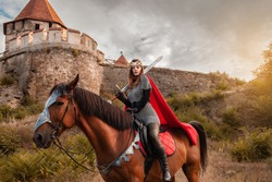 A beautiful girl in the costume of the warrior queen. A woman on horseback with a sword in her hand.