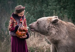 A beautiful girl in the Russian style costume feeding a real big brown bear in the forest. Late autumn period