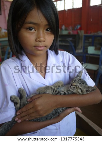 A beautiful girl is holding an adorable tabby kitty. The kitty is sleeping peacefully. She's love the tiny cat so much. #1317775343