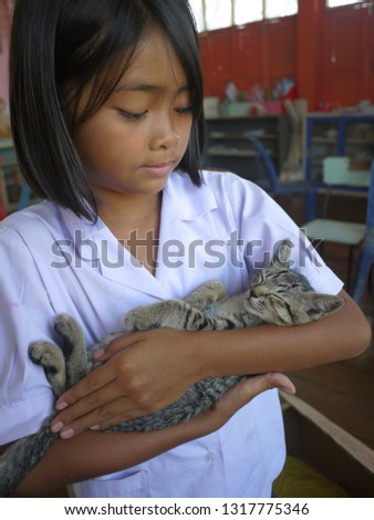 A beautiful girl is holding an adorable tabby kitty. The kitty is sleeping peacefully. She's love the tiny cat so much. #1317775346