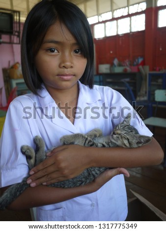 A beautiful girl is holding an adorable tabby kitty. The kitty is sleeping peacefully. She's love the tiny cat so much. #1317775349