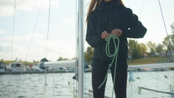 A beautiful girl on board a white yacht knits a sea knot on a rope in preparation for rafting on the river under sail