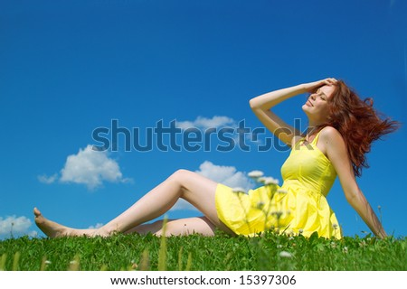 stock photo : A beautiful girl on yellow dress and with red hair enjoying summer