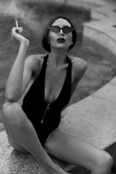 A beautiful girl smokes. A model with glasses.