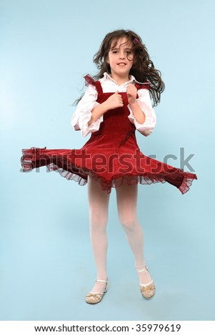 A beautiful girl spinning around in a red dress, on a blue studio background.