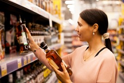 A beautiful girl takes alcoholic drinks from the supermarket shelf. Shopping for alcohol in the store.