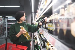 A beautiful girl takes alcoholic drinks from the supermarket shelf. Shopping for alcohol in the store. The girl chooses a drink in the supermarket.