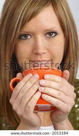 A beautiful girl warms her hands with a mug of hot cocoa. - stock photo