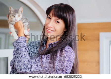 Stock Photo A beautiful girl with long black hair hugs a kitten. A model with clean skin. A gray kitten on his hands. Frontal to the animals.
