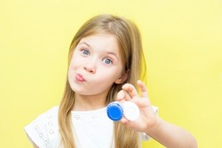 A beautiful girl with long hair holds a container with lenses in her hand. The concept of vision problems in children. Yellow background.