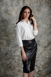 A beautiful girl with long hair in a black leather skirt and white blouse. Business style clothing. Business woman in a formal attire stands in the light room.