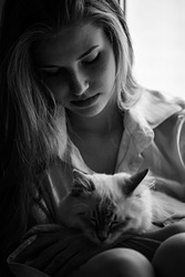 A beautiful girl with long hair is sitting on the windowsill and holding a kitten on her lap. The photo is black and white. Image with toning. Image with noise effects.Focus on the eyes.