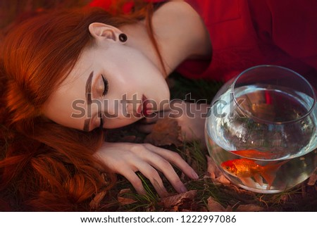Stock Photo A beautiful girl with long red hair in the rays of light sleeps next to a goldfish in an aquarium. Young redheaded woman Lein on an autumn meadow. Art work.