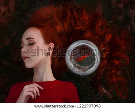 Stock Photo A beautiful girl with long red hair sleeps next to a goldfish in an aquarium. Young redheaded woman Lein on an autumn meadow. Art work.