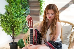 A beautiful girl with red curly hair sits on a chair with a seven-string guitar. Hippie girl in the Studio.
