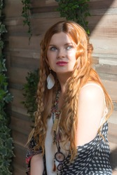 A beautiful girl with red curly hair stands at the wooden wall around the plan in the sunlight. Studio with wooden walls and green leaves.