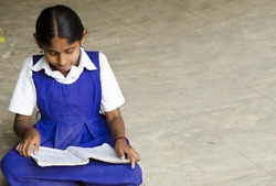 A beautiful girl writing in a village school