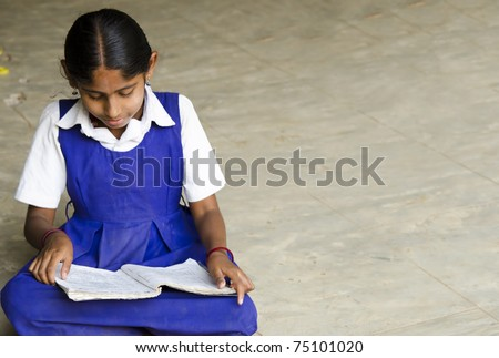 A beautiful girl writing in a village school