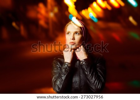 A beautiful glamour girl in jacket and muffler is standing in the city street at colored flares background.