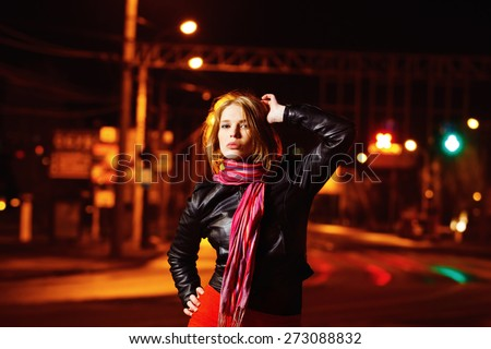 A beautiful glamour girl in jacket is standing in the city street at colored flares background.