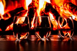 A beautiful glass with a drink near the fireplace. Firewood and fire. Glass and liquid.