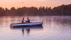 A beautiful golden sunset on the river. Lovers ride in a boat on a lake during a beautiful sunset. Happy couple woman and man together relaxing on the water. Unity of human being with nature.
