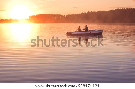 A beautiful golden sunset on the river. Lovers ride in a boat on a lake during a beautiful sunset. Happy couple woman and man together relaxing on the water. The beautiful nature around.  #558171121
