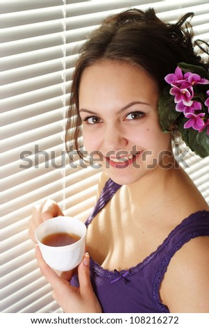 A beautiful good girl standing near a window with a cup and flower on a light background