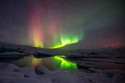 A beautiful green and red aurora dancing over the Jokulsarlon lake, Iceland.