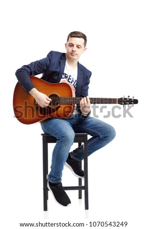 A beautiful guy in jeans and a blue jacket plays an acoustic guitar. Isolated on white background. Hipster style. #1070543249