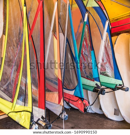 A beautiful hangar, boathouse, in which there are many sails for windsurfing and many other marine elements.
