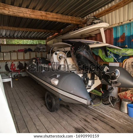 A beautiful hangar, boathouse, in which there is an inflatable boat with a motor and many other marine elements.