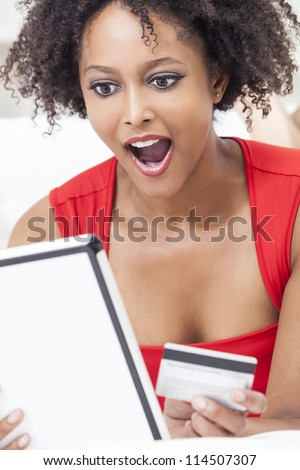 A beautiful, happy and surprised, mixed race African American girl or young woman laying down wearing a red dress using a tablet computer and credit card internet shopping on line