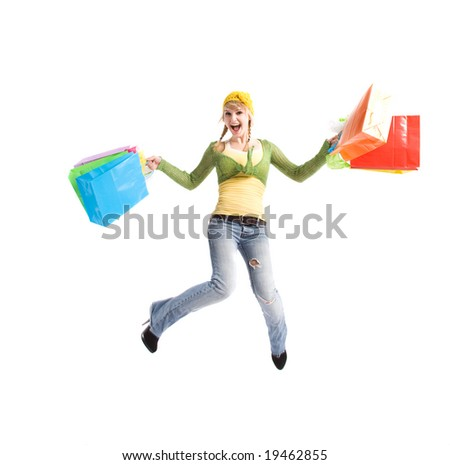 A beautiful happy caucasian girl jumping and carrying shopping bags