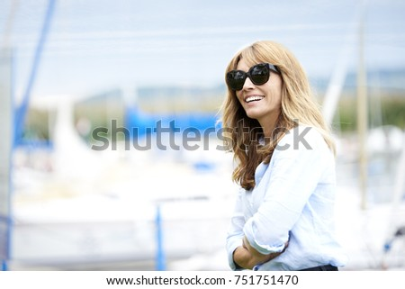 A beautiful happy middle aged woman standing outdoor and laughing. #751751470