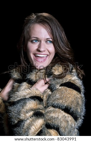 A beautiful, happy model wearing a fur coat.
