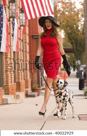 a beautiful happy woman walking her dalmatian puppy dog down the street