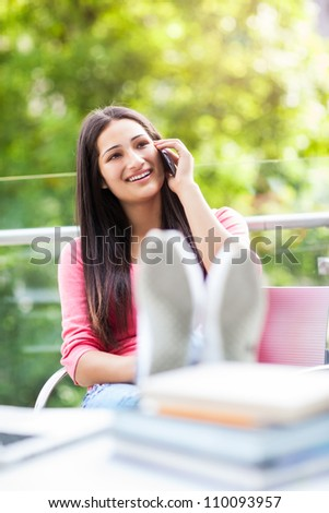 A beautiful hispanic college student talking on the phone on campus