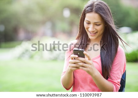 A beautiful hispanic college student texting on her cellphone - stock photo