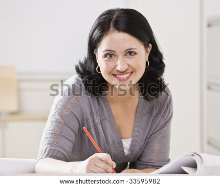 A beautiful Hispanic woman writing at a desk.  She is smiling at the camera.  Square compostion.