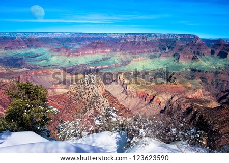 A beautiful image of the Grand Canyon during the early morning sunrise with a big partial moon in the sky.  Shot at the South Rim in wintertime.
