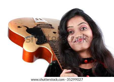 A beautiful Indian teenage girl with an acoustic guitar, on white studio background.