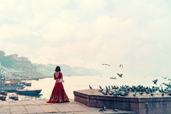 A beautiful Indian woman in a red Sari stands alone on the street. There is a flock of pigeons on the pedestal. In the background is a river and a view of the city. Copy space. Travel and culture