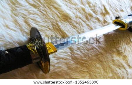 A beautiful katana being unsheathed. The furry texture looks almost like waves rippling underneath the glistening sword.