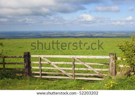 a beautiful landscape in springtime with a view over a wooden gate to a lush green meadow and the vale of york in the distance