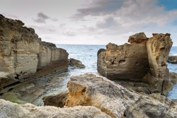 A beautiful landscape view of sedimentary sandrock rock formations by the blue green sea on a cloudy day at the impressive coast of mediterranean llucmajor in Mallorca island spain balearic