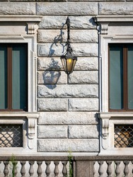 A beautiful lantern hangs on the wall of an old building. The lantern is on. Parts of the windows, bars under the windows and part of the fence near the house are visible. Vertical background.