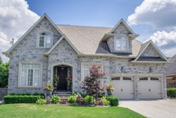 A beautiful large modern custom executive residential house with grey stone and brick, with gray shingles and grey trim, patterned interlock walkway and driveway, and double garage doors.
