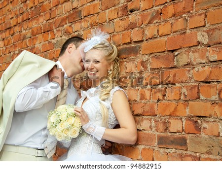 A beautiful laughing bride and a slender groom speak near the wall; wedding day